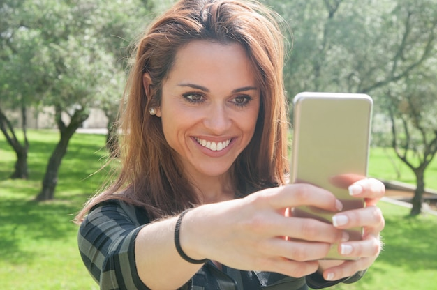 Frohe aufgeregte junge frau, die selfie im park nimmt Kostenlose Fotos