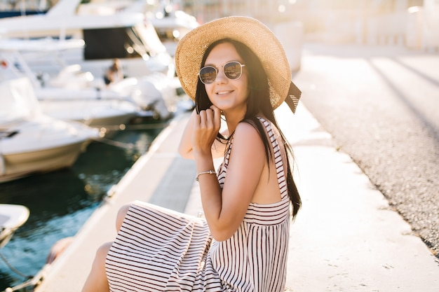 Frohe dunkelhaarige dame mit hut, die zeit im seehafen verbringt und an sonnigem tag irgendwo in europa sonnenschein genießt Kostenlose Fotos