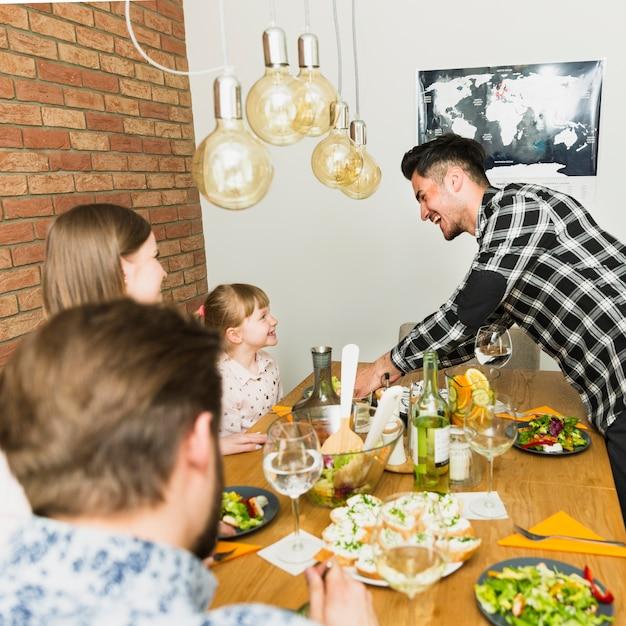Frohe familie, die am tisch sitzt Kostenlose Fotos