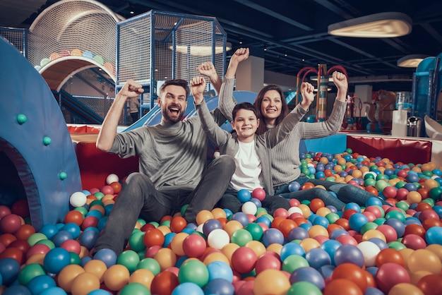 Frohe familie, die im pool mit bällen sitzt Premium Fotos