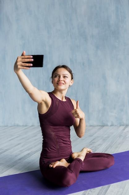 Frohe frau, die ein foto auf ihrer yogasitzung macht Kostenlose Fotos