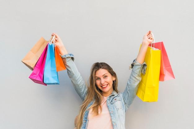 Frohe frau, die mit einkaufstaschen an der hellen wand steht Kostenlose Fotos