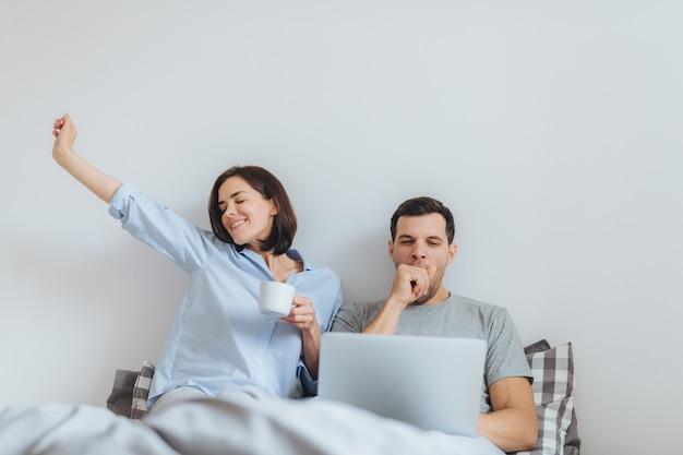 Frohe frau liegt im bett, trinkt heißen kaffee und ihr mann arbeitet die ganze nacht am laptop Premium Fotos