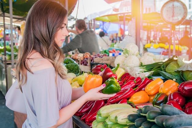 Frohe frau wählt grüne und rote paprika im supermarkt. einkaufen. frau wählt bio-lebensmittel obst pfeffer paprika im grünen markt Kostenlose Fotos