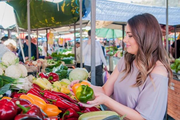Frohe frau wählt grüne und rote paprika im supermarkt shoppin Kostenlose Fotos