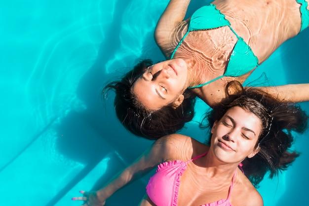 Frohe freundinnen, die im pool schwimmen Kostenlose Fotos