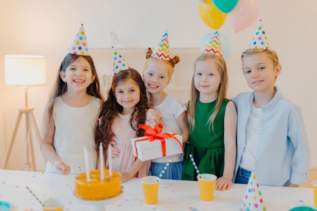 Frohe geburtstagskind steht mit presenet, glückliche freunde kommen, um ihr zu gratulieren, tragen partykegelhüte, stehen in der nähe von festlichem tisch mit kuchen Premium Fotos