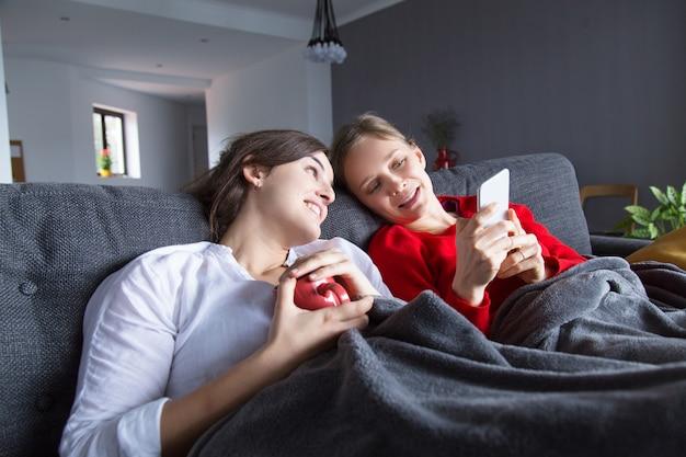 Frohe homosexuelle mädchen, die auf couch stillstehen Kostenlose Fotos