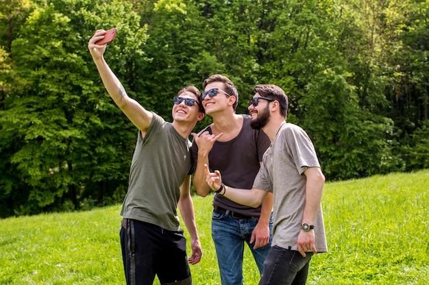 Frohe junge männer, die selfie in der natur nehmen Kostenlose Fotos