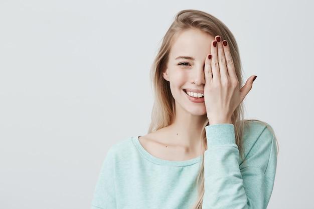 Frohe kaukasische frau mit langen gefärbten haaren, hellblauem pullover tragend, ihr auge mit der hand schließend. glückliche positive frau, die gute und verspielte stimmung hat. Kostenlose Fotos