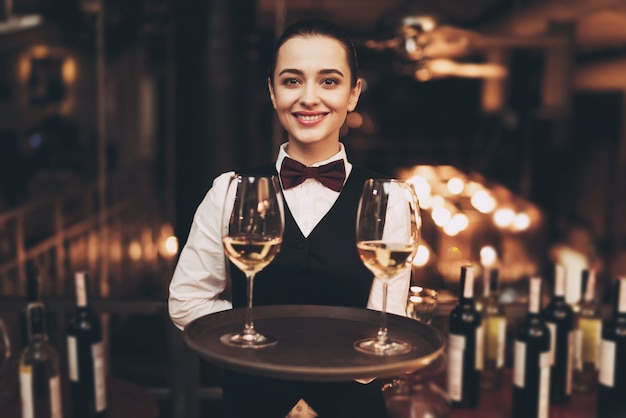 Frohe kellnerin, die behälter mit gläsern weißwein hält. Premium Fotos