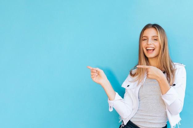 Frohe recht junge frau, die ihre finger gegen blauen hintergrund zeigt Kostenlose Fotos