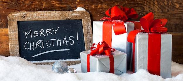 Frohe weihnachten auf einer tafel mit geschenken, panoramablick. Kostenlose Fotos