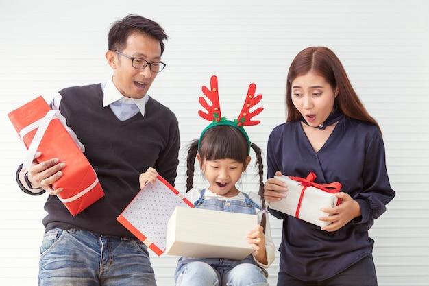 Frohe weihnachten familie und fröhliche feiertage. mutter und vater überraschen mit kindern. tochter und elternteil, die anwesendes geschenk am weißen wohnzimmer halten. Premium Fotos