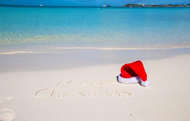 Frohe weihnachten geschrieben auf weißen sand des tropischen strandes mit weihnachtshut Premium Fotos
