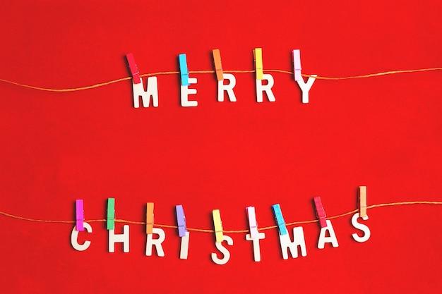 Frohe weihnachten grußnachricht mit wäscheklammern auf roter oberfläche Premium Fotos