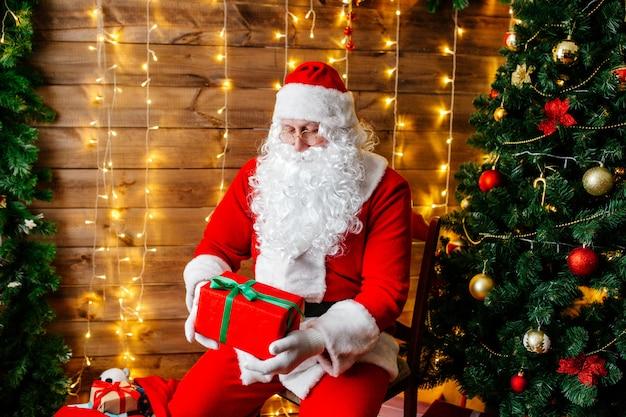 Frohe weihnachten, santa claus nahe weihnachtsbaum mit geschenken Premium Fotos