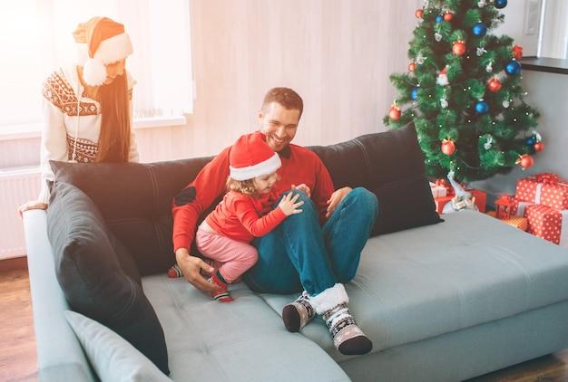 Frohe weihnachten und ein glückliches neues jahr. familienfoto. junger mann sitzt mit tochter auf sofa Premium Fotos