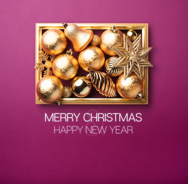 Frohe weihnachten und ein glückliches neues jahr. glänzender goldweihnachtsdekorationsball und -stern mit goldenem rahmen im purpur Premium Fotos