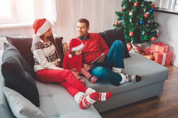 Frohe weihnachten und ein glückliches neues jahr. ruhiges und friedliches parenst, das auf sofa mit kind liegt. sie schauen sich an. man lächelt. er hält tablette. mädchen schaut es an. Premium Fotos