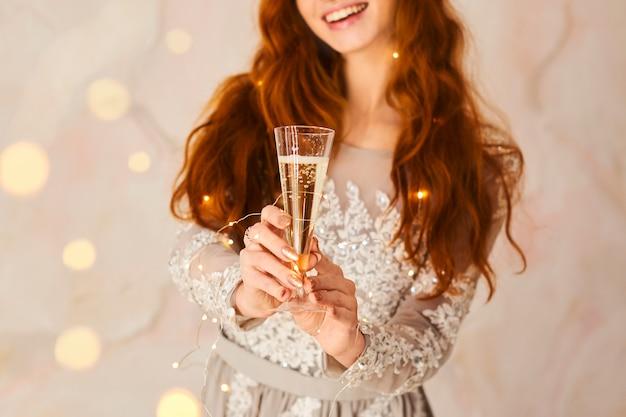 Frohe weihnachten und ein gutes neues jahr! nette nette junge frau hält ein glas mit champagner und beglückwünscht mit weihnachten zuhause Premium Fotos