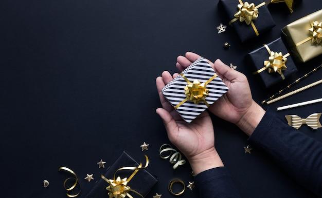 Frohe weihnachten und neujahrsfeierkonzepte mit personenhand, die geschenkbox und verzierung in goldener farbe auf dunklem hintergrund hält. wintersaison und jubiläumstag Premium Fotos