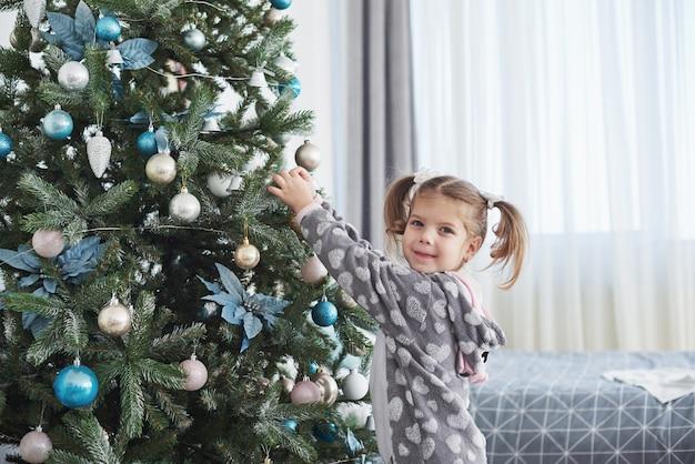 Frohe weihnachten und schöne feiertage! junges mädchen, das hilft, den weihnachtsbaum zu verzieren und etwas weihnachtsflitter in ihrer hand hält Premium Fotos