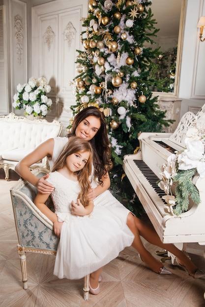 Frohe weihnachten und schöne feiertage. nette mutter und ihr nettes tochtermädchen im weißen klassischen weißen innenklavier und in einem verzierten weihnachtsbaum. neujahr Premium Fotos