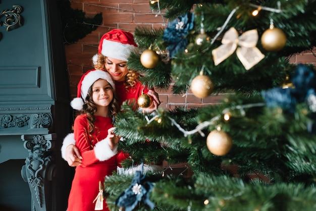 Frohe weihnachten und schöne feiertage! schöne mutter mit kleiner tochter in weihnachtskostümen verbringen zeit zusammen nahe dem weihnachtsbaum. Premium Fotos