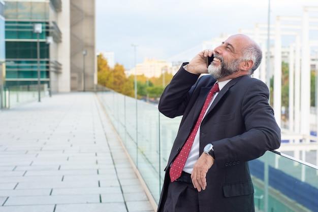 Froher entspannter reifer geschäftseigentümer, der auf mobiltelefon spricht Kostenlose Fotos