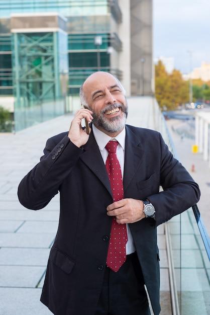 Froher erfolgreicher reifer geschäftsmann, der auf mobiltelefon spricht Kostenlose Fotos