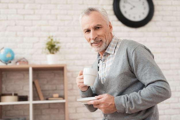Froher trinkender kaffee des älteren mannes zu hause. Premium Fotos