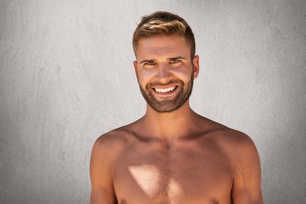 Frohes bodybuilder mit bizeps, der oben ohne mit angenehmem lächeln posiert und glücklich ist, freizeit im fitnessstudio zu verbringen Kostenlose Fotos