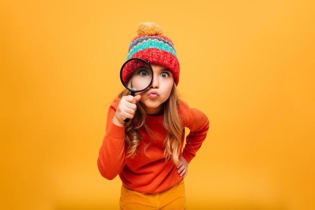 Frohes junges mädchen in der strickjacke und in hut, welche die kamera mit vergrößerungsglas über orange betrachten Kostenlose Fotos