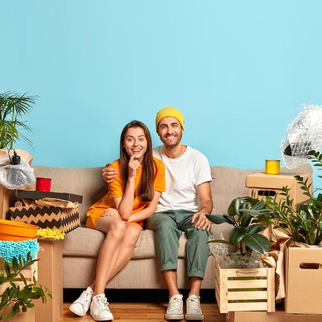 Frohes junges paar, das auf der couch sitzt, umgeben von kisten Kostenlose Fotos