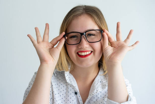 Frohes mädchen mit den roten lippen tragende gläser genießend Kostenlose Fotos