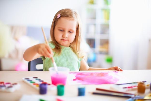 Frohes mädchenkind zeichnet gouache in den verschiedenen farben auf ein weißes blatt papier. Premium Fotos