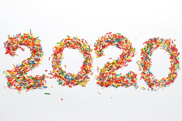 Frohes neues 2020 jahr. bunte zahlform mit hellem regenbogenzucker besprüht lokalisiert auf weiß Kostenlose Fotos