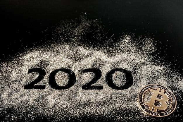 Frohes neues jahr 2020. die kreative collage aus den zahlen zwei und null bildete das jahr 2020. schöne funkelnde goldene zahl 2020 und bitcoin auf schwarz Premium Fotos