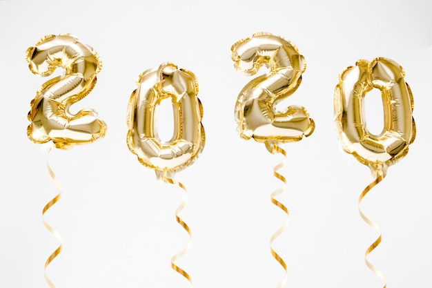 Frohes neues jahr 2020 feiern. goldfolie steigt die nr. 2020 im ballon auf, die in der luft auf weißem hintergrund hängt Premium Fotos