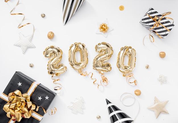 Frohes neues jahr 2020 feiern. goldfolie steigt nr. 2020 auf weißem hintergrund mit geschenken im ballon auf Premium Fotos