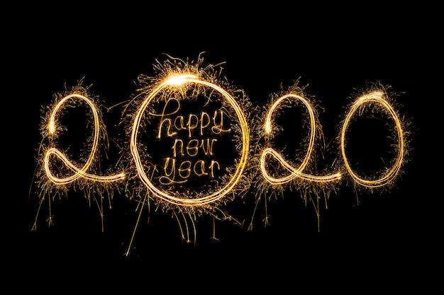 Frohes neues jahr 2020. kreativer text frohes neues jahr 2020 geschrieben funkelnde wunderkerzen Premium Fotos