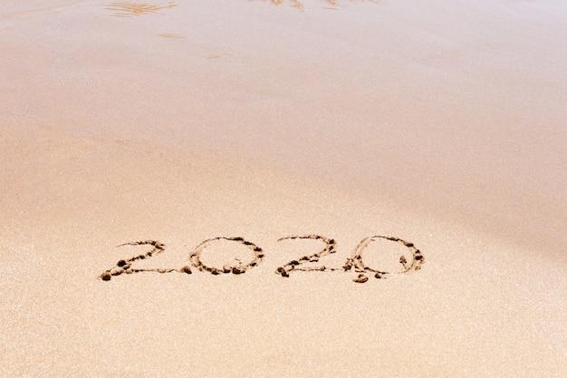 Frohes neues jahr 2020 text am strand. urlaub planen. Premium Fotos