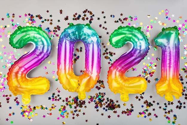 Frohes neues jahr 2021 hintergrund. regenbogenfarben der metallischen luftballons auf weiß. flache lage, draufsicht Premium Fotos