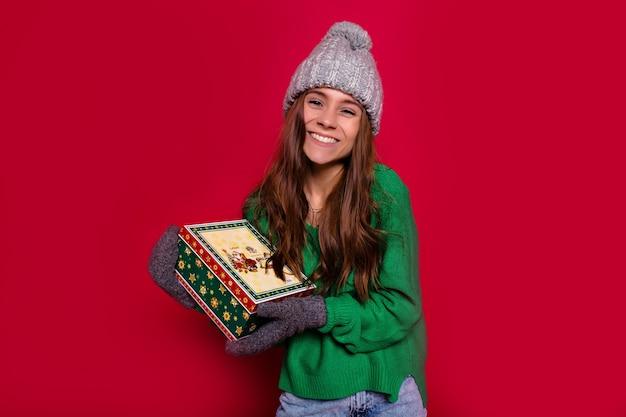 Frohes neues jahr partyzeit der lächelnden schönen jungen frau, die ein geschenk zur kamera auf rotem hintergrund hält. nettes lächeln, winterpullover und mütze, spaß haben, geburtstagsfeier Kostenlose Fotos