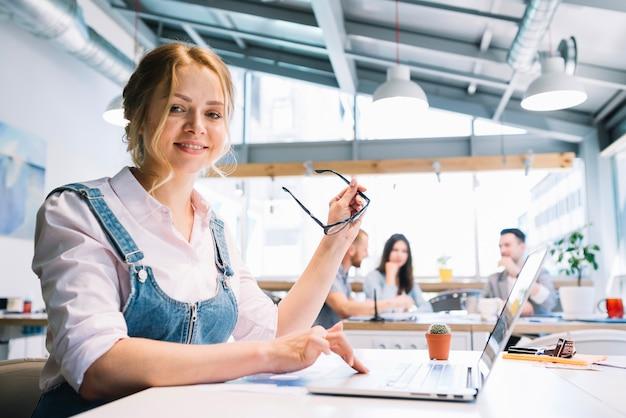 Fröhliche Büroarbeitsfrau mit Brille Kostenlose Fotos
