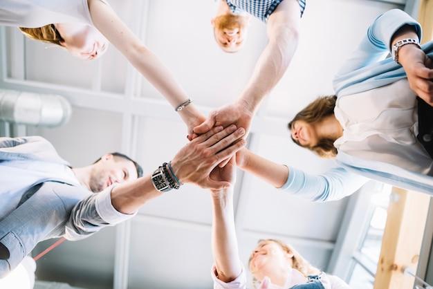 Fröhliche Menschen, die Hände zusammen im Büro halten Kostenlose Fotos
