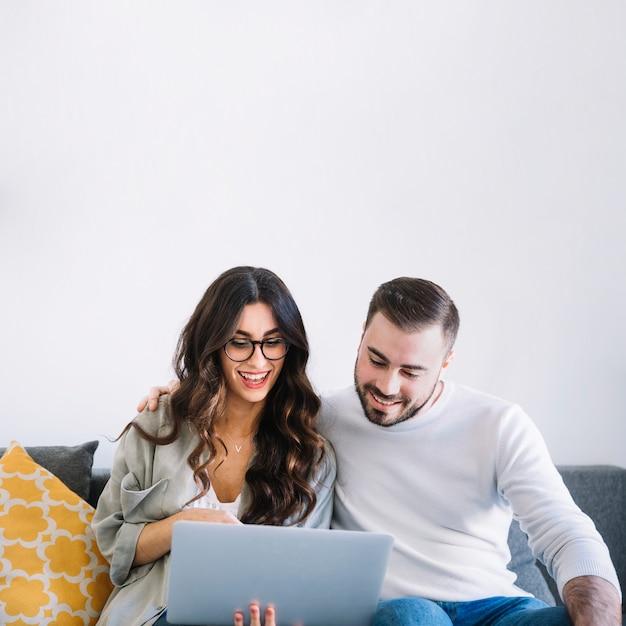 Fröhliche Paare mit Notizbuch auf Sofa Kostenlose Fotos