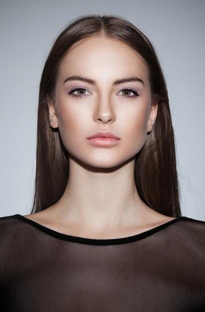 Frontalporträt eines schönen brünetten mädchens, das nacktes make-up trägt Premium Fotos