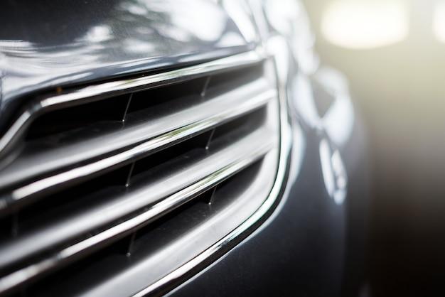 Frontautogrill eine schwarze farbe mit angemessenem licht der reflexion und undeutlichem hintergrund Premium Fotos